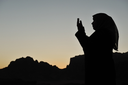femme musulmane: silhouette d'une femme musulmans priant dans le d�sert Banque d'images