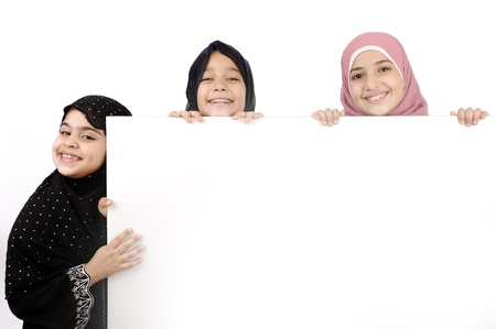 fille arabe: Trois petites écolières tenant un panneau blanc pour votre message. Bonne pour les bordures des articles ou des sites Web. Beaux modèles arabo-musulmane. Isolé sur fond blanc.