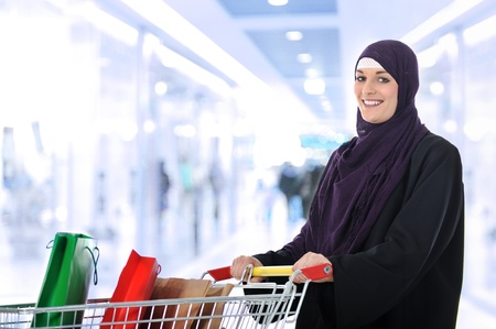 Image of pretty muslim woman with cart looking at camera and smiling photo