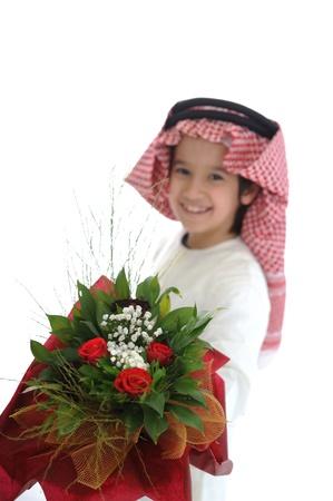 gulf: Cute arabic little boy with bouquet of flowers Stock Photo