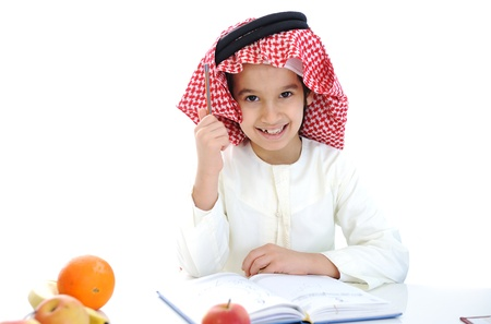learning arabic: Arabic kid at school table with notebook and apple snack Stock Photo