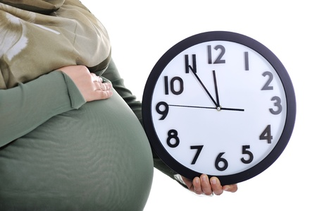 Tummy of pregnant muslim woman with clock photo