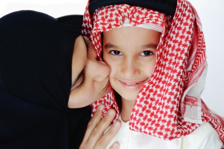 Arabic Muslim mother kissing her little son photo