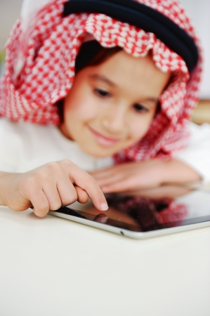 Arabic little boy playing on tablet photo