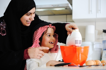 assisting: Muslim mother and little son in the kitchen Stock Photo