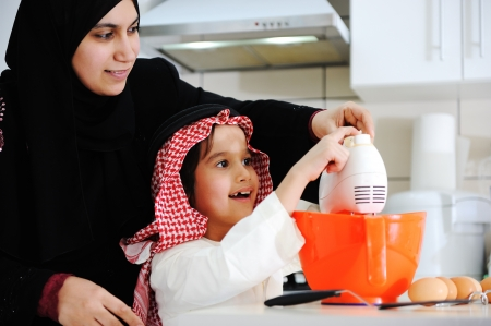 learning arabic: Muslim mother and little son in the kitchen Stock Photo