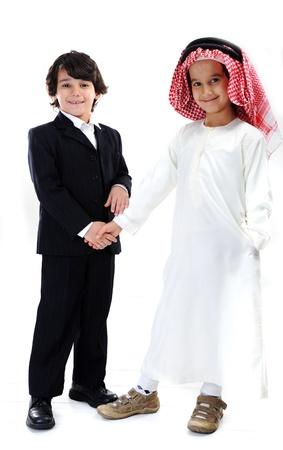 niños de diferentes razas: Árabe y pequeños empresarios caucásica apretón de manos Foto de archivo