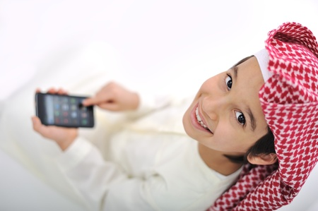 Kid with traditional middle eastern clothes playing with smart phone 스톡 콘텐츠