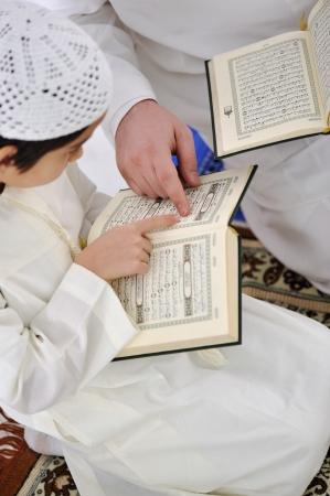 Muslim Arabic father and son reading Koran
