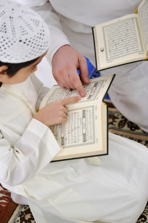 Muslim Arabic father and son reading Koran