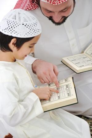 Muslim Arabic father and son recitating Koran photo