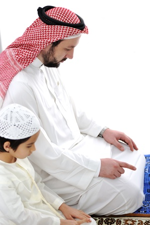 praying together: Arabic father and son praying together Stock Photo