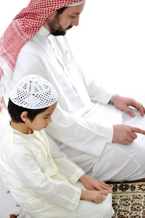 praying together: Muslim father and son praying together Stock Photo