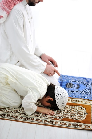 Saudi arabian father and son praying together photo