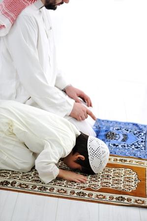 Saudi arabian father and son praying together