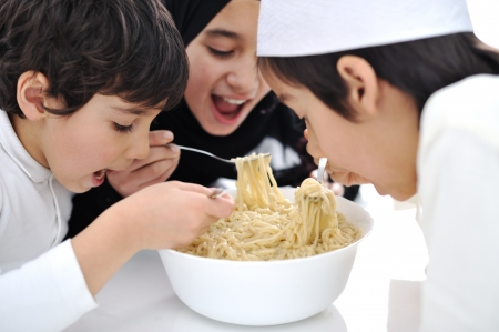 Three Arabic children eating together photo