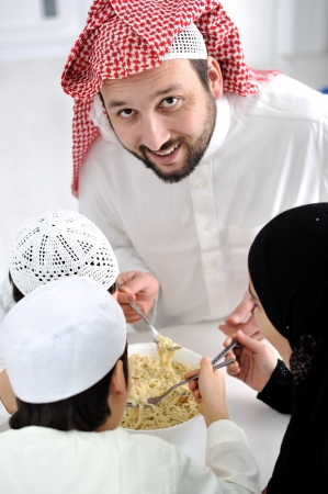 Arabic muslim family eating  at home together, father and kids Stock Photo - 22127276