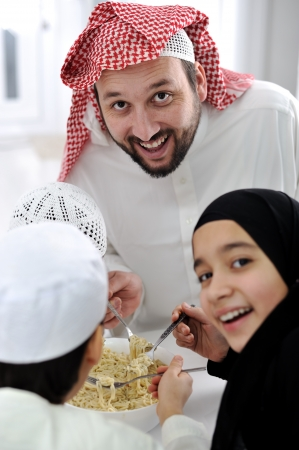 Arabic muslim family eating  at home together, father and kids  photo