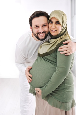 Portrait of a happy young pregnant muslim woman with her husband photo