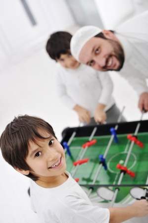 Arabic family playing at home together, father and kids photo