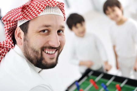 Arabic muslim family playing at home together, father and kids  photo