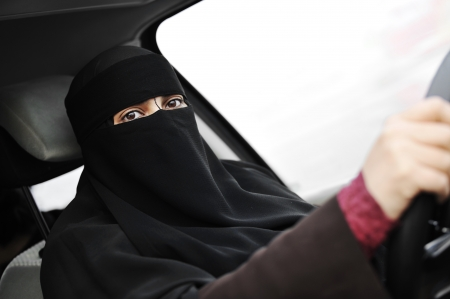 auto leasing: Arabic Muslim woman with veil and scarf (hijab and niqab) driving car