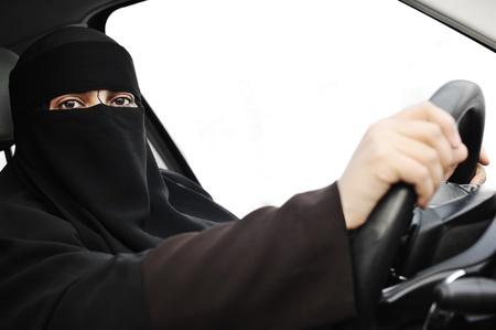 niqab: Arabic Muslim woman with veil and scarf (hijab and niqab) driving car