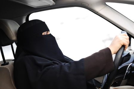 woman driving car: Arabic Muslim woman with veil and scarf (hijab and niqab) driving car