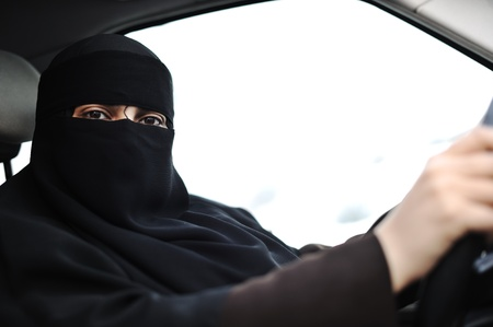 Arabic Muslim woman with veil and scarf (hijab and niqab) driving car
