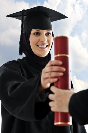 Young arabic muslim female graduating and receiving diploma photo