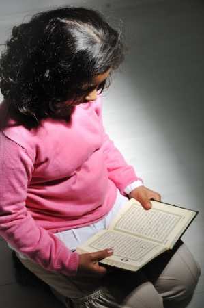 petite fille musulmane: Petite fille musulmane est rading un houx Coran Banque d'images