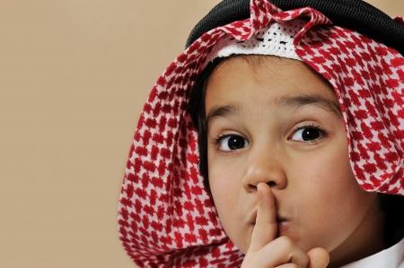Cute arabian kid saying psst, silence please photo