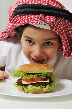 middle eastern clothes: Arabic kid with burger