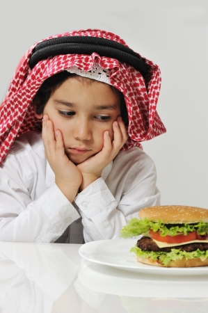 Unhappy Arabic kid with burger photo