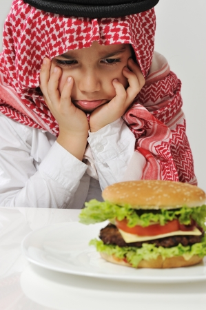 Angry Arabic kid with burger photo