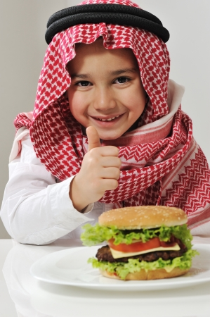 middle eastern clothes: Little boy with burger Stock Photo