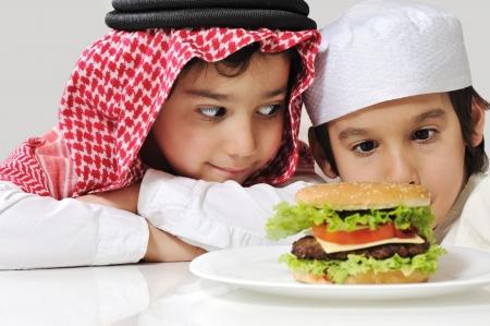 Arabic two little kids with big Burger Reklamní fotografie