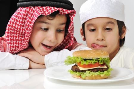 comida arabe: Medio Oriente dos niños pequeños con gran hamburguesa