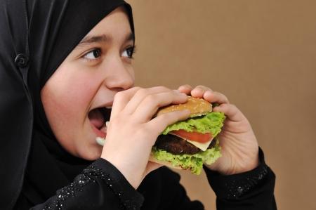 fille arabe: Arabian fille mangeant hamburger