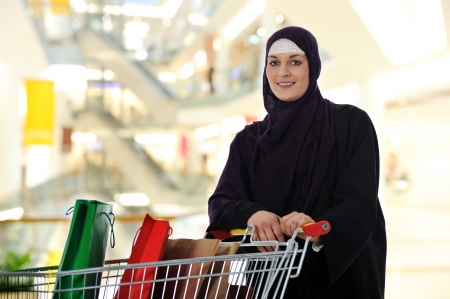 Image of pretty muslim woman with cart looking at camera photo