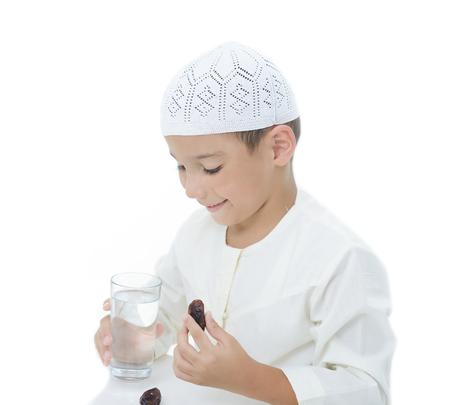 A little muslim boy wearing islamic attire ready for braking Ramadan fast 스톡 콘텐츠