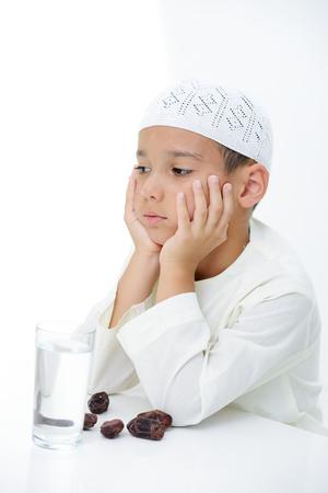 Een beetje moslim jongen die islamitische kledij klaar voor het remmen ramadan Stockfoto