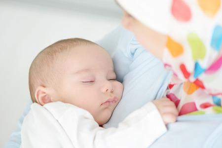 Mooie baby van twee maanden oud in zijn moslim moeders handen.