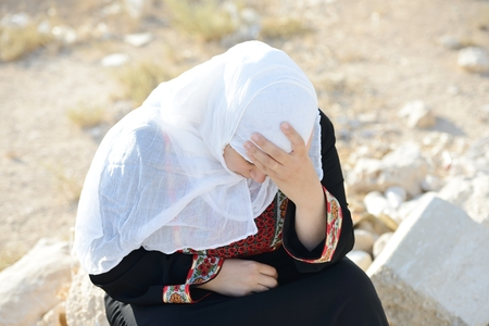 insurrection: Desperate Arabic woman sitting on rock and crying Stock Photo