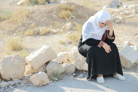 Desperate Arabic woman sitting on rock and crying 스톡 콘텐츠