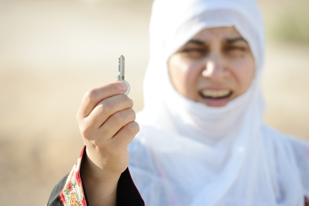 insurrection: Desperate Arabic woman on Middle East holding key of lost home Stock Photo