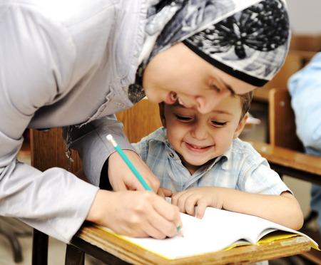 Female Muslim teacher helping a little pupil in the classroom
