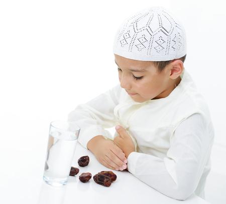 穿伊斯兰教的一位小穆斯林男孩准备好塑造ramadan
