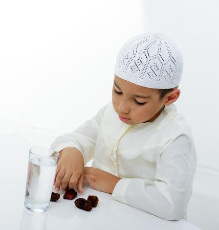 ksa: A little muslim boy wearing islamic attire ready for braking Ramadan fast Stock Photo