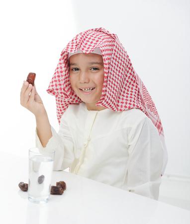 arabian food: A little muslim boy wearing islamic attire ready for braking Ramadan fast Stock Photo
